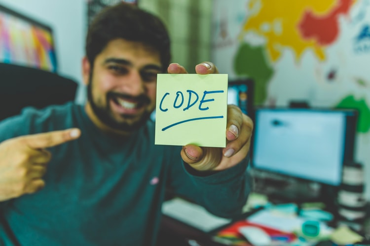 """man holding a paper written with """"Code"""""""